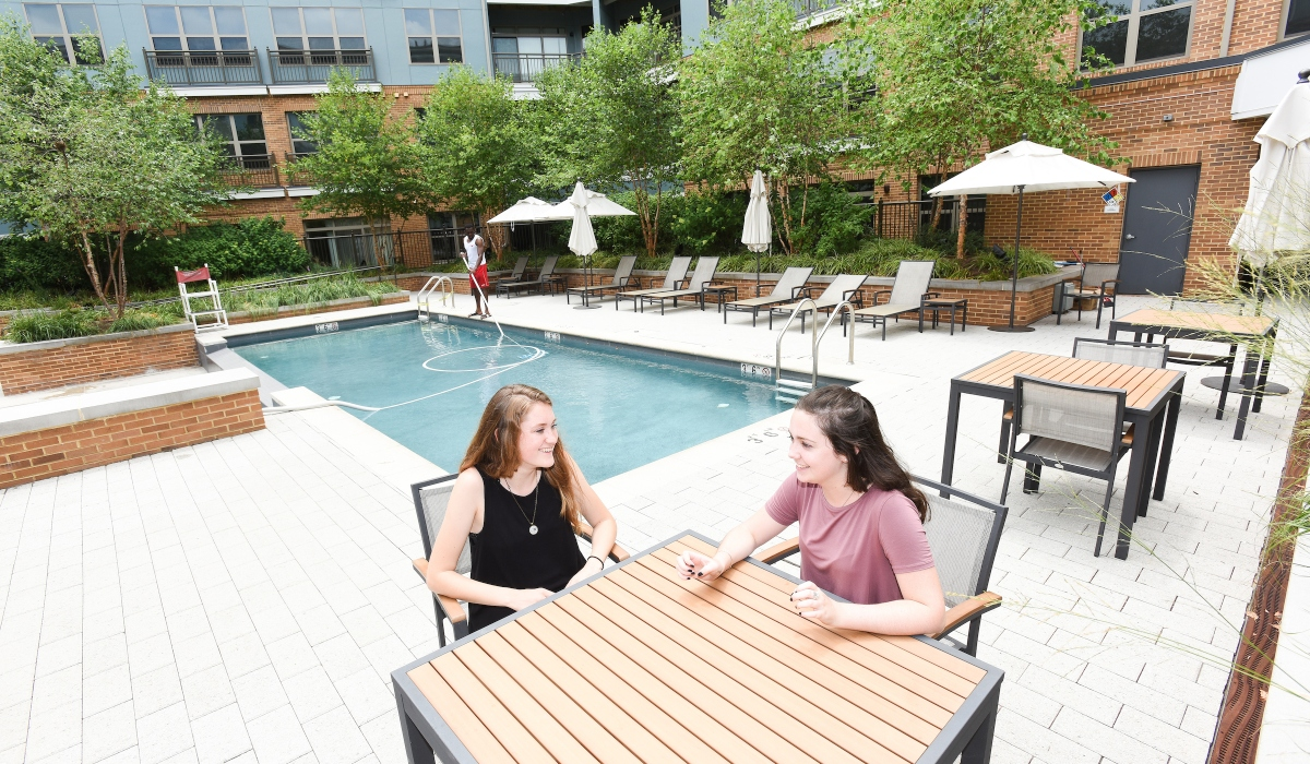 Female students sitting by pool in apartment complex