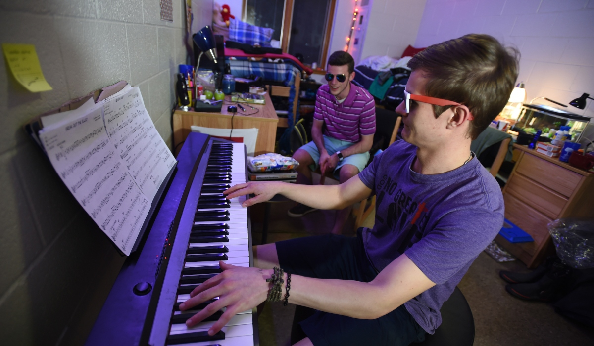Student playing keyboard in his room with a friend.
